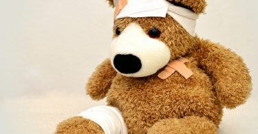 Kind krank in Neuseeland Teddy mit Binden